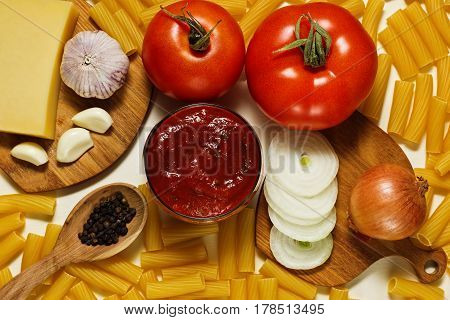 Different raw ingredients: dry pasta tomatoes tomato and basil sauce onion garlic pepper and parmesan cheese