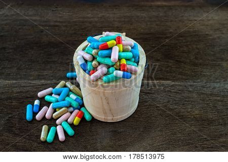 Many colorful medicines expire in basket on wooden background with copy space
