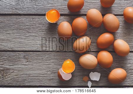 Fresh chicken brown home eggs with cracked eggshell and yolk on rustic wood table. Top view with copy space. Rural still life, natural healthy food and organic farming concept.