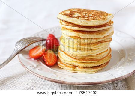Pancakes with strawberries on light textile surface