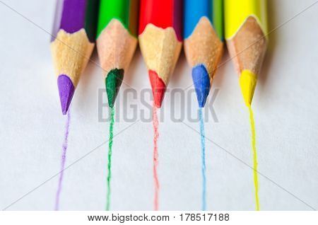 Set of colored pencils isolated against the white background. Pencils drawed lines of corresponding color. Close up, left to right, selective focus