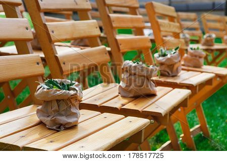 Outdoor wedding ceremony decoration with greenery. Wooden chairs decorated with green botanic arrangements, seating for guests, rustic style