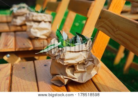 Outdoor wedding ceremony decoration details closeup. Wooden chairs decorated with green botanic arrangements, seating for guests, rustic style