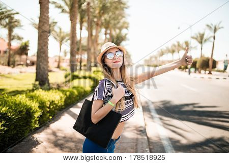 Beautiful And Young Girl Stops The Car Around The Palm Trees And The Road . Summer Vocation