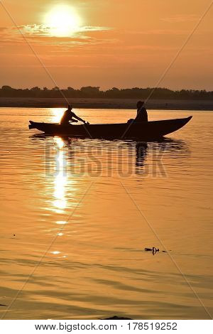 VARANASI, INDIA - July 7, 2014 : Fishermen on wooden boats at Ganges river in Varanasi India taken on July 7, 2017 at Varanasi, India. Due to Ganges river Indian civilization thrived from ancient times