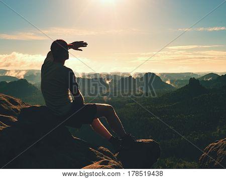 Man Sit On Peak Of Rock. Hiker Shadowing Eyes With Raised Arm