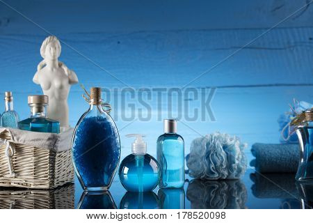 Spa concept - Venus de Milo statue and bottles with cosmetics on glass table and blue background
