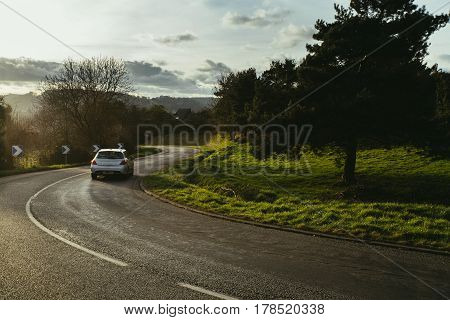 Asphalt Road With Cars Passing Through The Forest In The Region Of Normandy, France. Landscape In Au