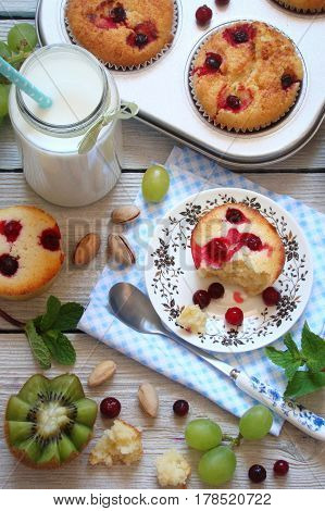 Muffins with cranberries fruit and milk for Breakfast on a light background