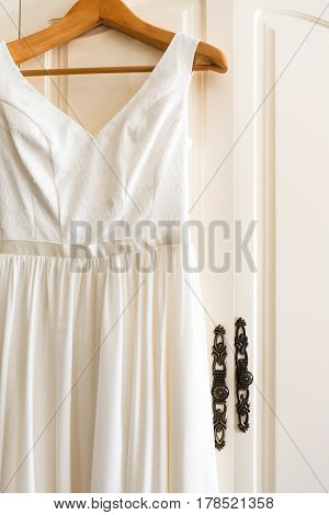 Wedding dress, clothing details, morning of bride. Beautiful white bridal gown on hanger, nobody, objects, indoors