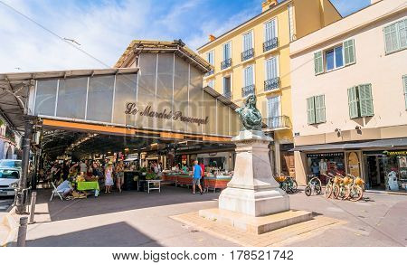 Antibes, France - June 29, 2016: day view of roofed market hall with unidentified tourists in Antibes France. There take place a typical Provencal market with about 50 stalls regularly every Tuesday until sunday
