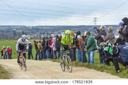 VendomeFrance- March 72016:Two cyclists ( Gregory Rast and Lawson Craddock )riding on a dirty roadTertre de la Motte in Vendome during the first stage of Paris-Nice 2016.