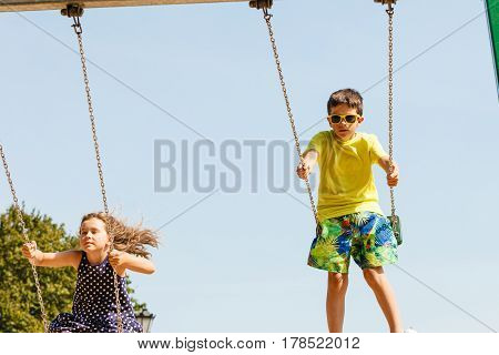 Fun and joy of children. Little girl and boy playing outdoor on preschool playground garden. Kids swinging on swing-set to touch the sky.