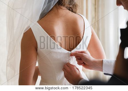 Bridal morning, bride wears dress. Groom helping fiancee to get dressed, adjusting buttons on wedding gown, rear view. close-up, crop
