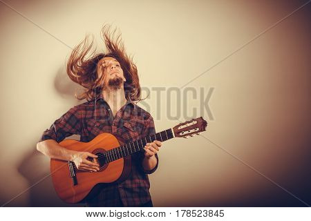 Music hobby passion concept. Enthusiast playing the instrument. Musician is giving the performance with his guitar.