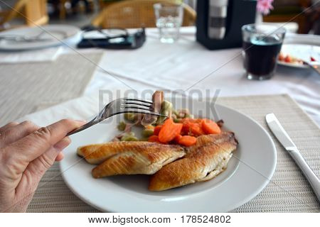Grilled fish fillet with soybeans and ham on a white plate.