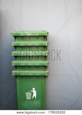 Stack of green industrial trash bins on plain wall background