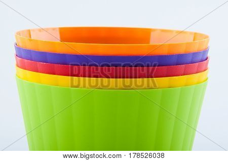Pile of green yellow red purple orange color plastic flower pots on white background