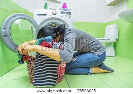 Woman tired of washing. She's lying on the laundry basket.