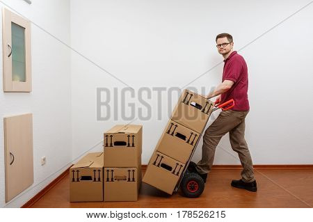 Man pushes a sack barrow. He is about to move heavy boxes.