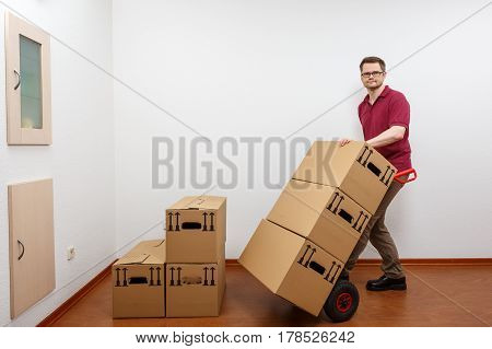 Man pushes a sack barrow heavy boxes.