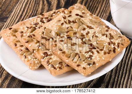 crispy bread with seeds of sunflower, flax and sesame seeds on a dark wooden background.