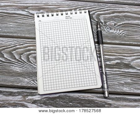 Notebook with blank sheets and pen on a wooden table. Mock up photo on timbered background.