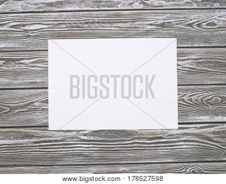 Clean sheet of paper on a wooden table. Mock up photo on timbered background.