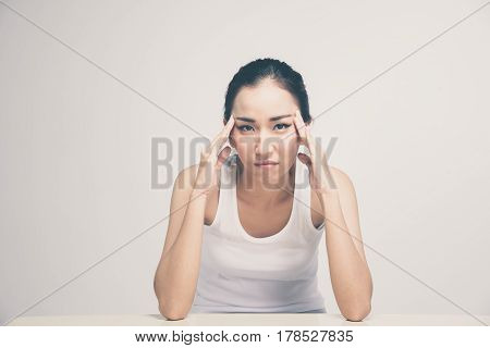Asian young woman with posture strain have a headache on white background dark tone