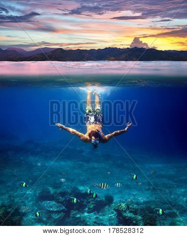 Underwater shoot of a young man snorkeling in a tropical sea and colorful sunset splitted by waterline. Design template