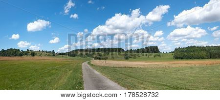 Way through meadows and fields in a rural landscape in summer with blue and white sky