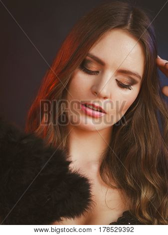 Woman beauty female face eyes makeup holding carnival feather fan in hand. Party new year celebration concept.