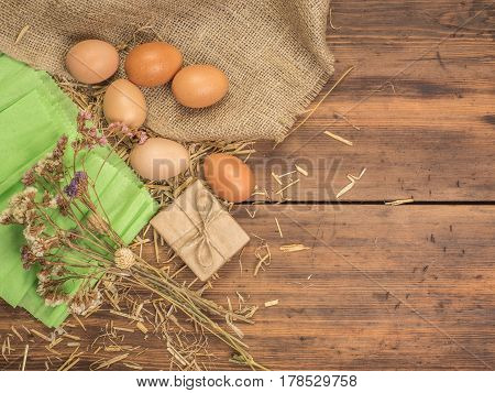 Rural creative background with brown eggs, burlap, straw, green paper and dry flowers on wooden table from old planks. Vintage, rustic background for Easter postcards, restaurant menus or advertising