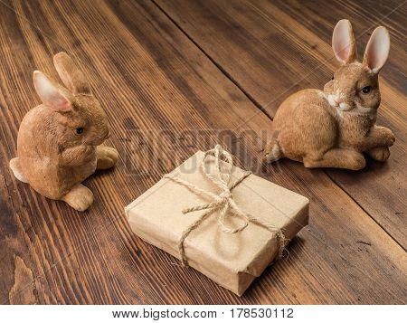 Easter bunnies on the background of wooden table from the old boards with gift box tied with string. Background in rustic style for advertising or Easter greetings