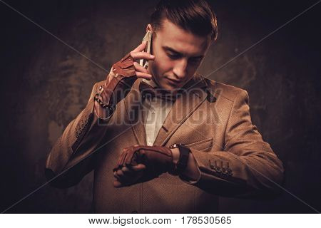 Sharp dressed man with mobile phone wearing jacket and bow tie