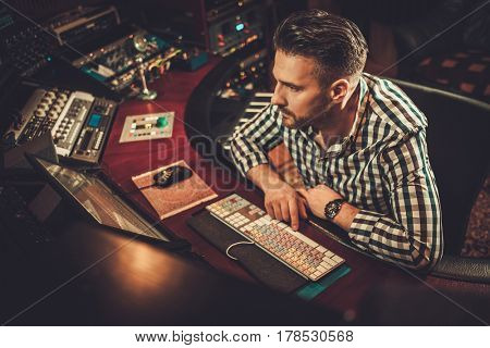 Sound engineer working in boutique recording studio.