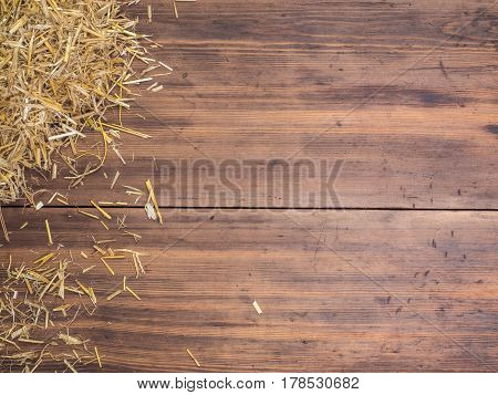 Rural eco background with and straw on the background of old wooden planks. The view from the top. Creative background for greeting cards, menu or advertising