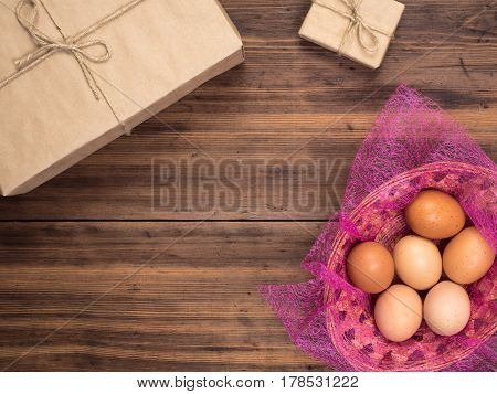 Easter eggs in the basket on the background of wooden table from the old boards with gift boxes, top view. Background with copy-space in rustic style for advertising or Easter greetings