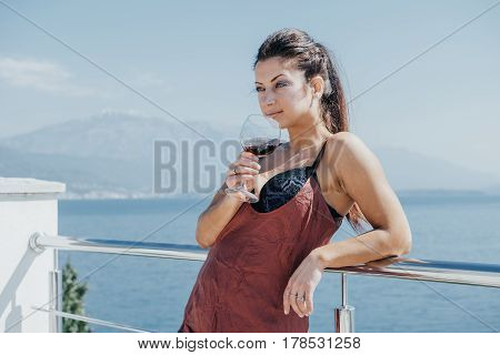 Pretty Woman In Glam Underwear  With A Glass Of Red Wine In Her Hand. Resort And Spa Concept.