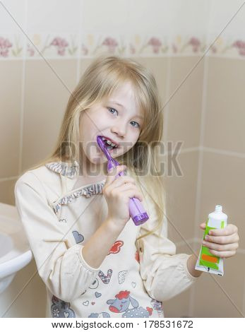 Cheerful girl brushing her teeth in the bathroom new toothbrush. The concept of oral care.