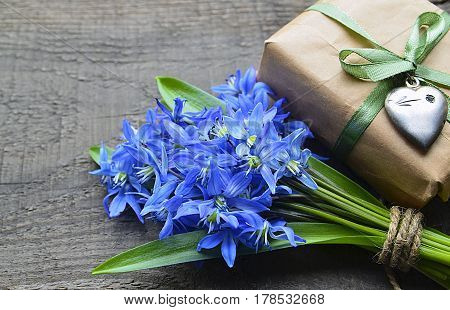 Bouquet of Blue Scilla (Squill) flowers and gift box with vintage silver heart on old wooden table.Happy Mother's Day or Spring holidays decoration.Spring flowers for Mother's Day.Selective focus.