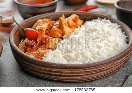 Chicken tikka masala with rice in bowl, close up