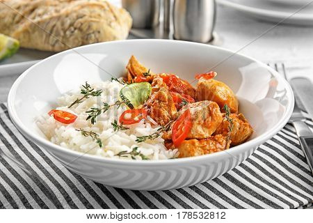 Plate with chicken tikka masala and rice on white table