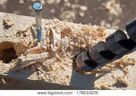 Steel boer drill a hole in a wooden board. Variety of carpentry tools and locksmith instruments close-up. Joinery work.