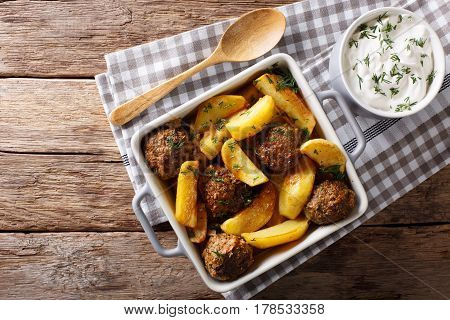 Baked Meat Balls With Potato Wedges And Sour Cream Sauce Close-up On The Table. Horizontal Top View