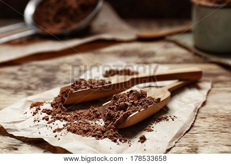 Wooden spoons with cocoa powder on paper napkin
