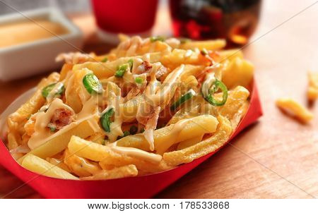 Portion of delicious french fries with bacon and cheese sauce, closeup