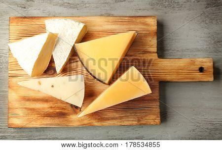 Board with delicious cheese on wooden table