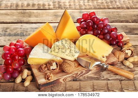 Board with variety of cheese on wooden background