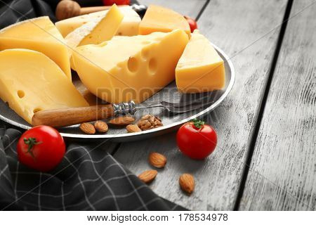 Tray with delicious cheese, tomatoes and nuts on wooden table